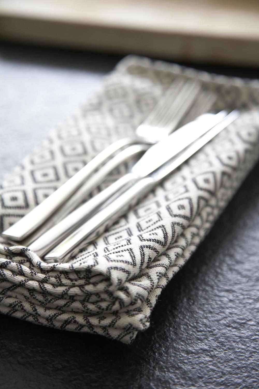 Classic Contemporary Victorian Kitchen Extension | Tori Muprhy napkin and silver crockery on Black Anticato worktop.